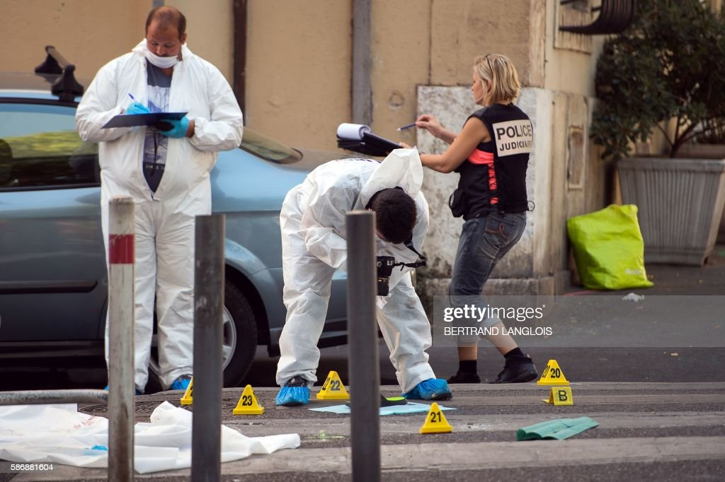 Forensic police officers and a criminal investigator investigate by the car where two men in their twenties were shot dead near the train station...