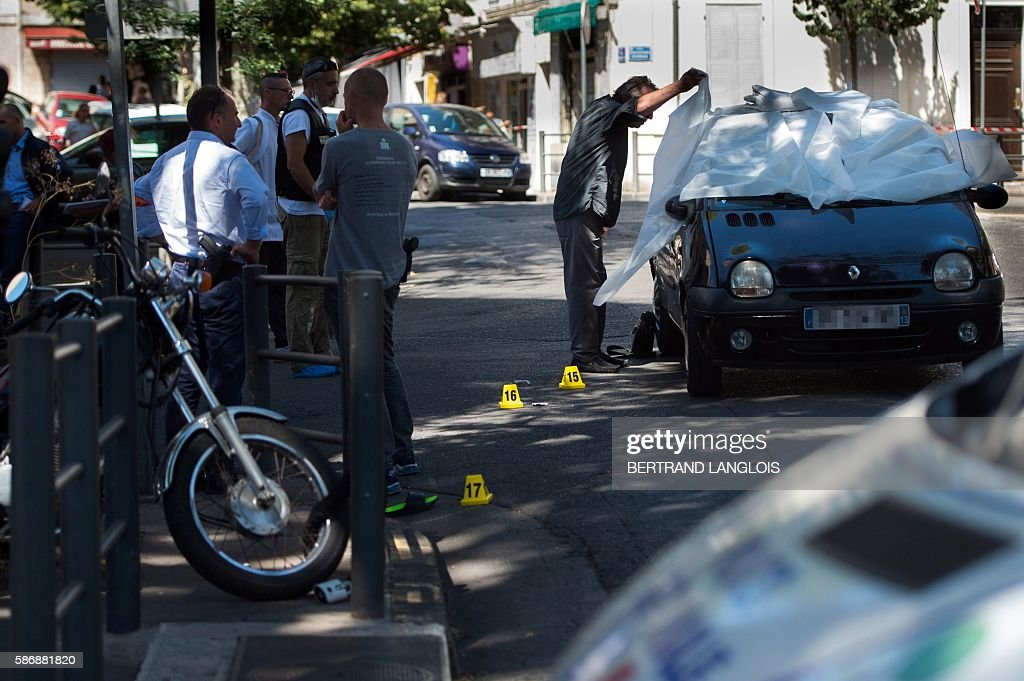 Forensic police officers and police officers investigate by the car where two men in their twenties were shot dead near the train station...