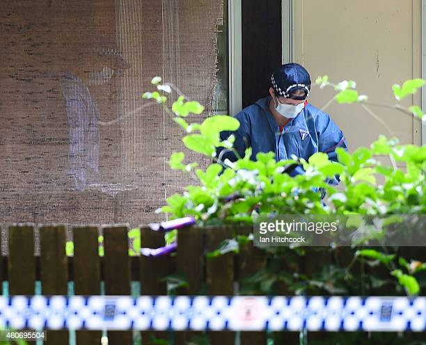 Forensic police officers attend the scene of a multiple stabbing in the suburb of Manoora on December 20 2014 in Cairns Australia Eight children have...