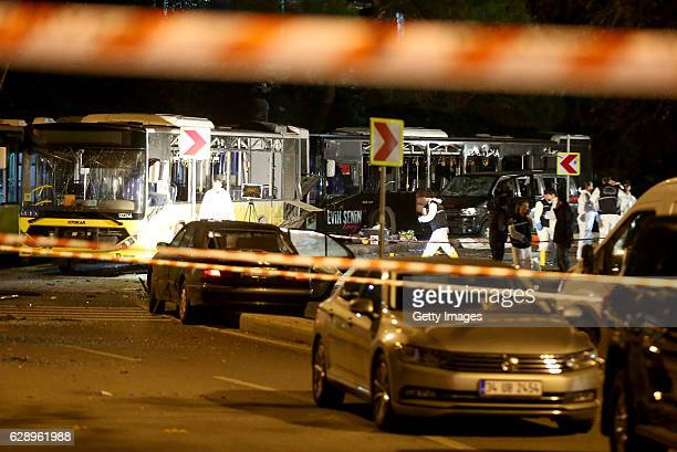 Forensic police officers inspect a group of damaged buses which were transporting riot policemen after the football match between Besiktas and...