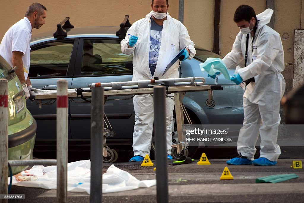 Forensic police officers investigate as a member of the emergency service arrives with a stretcher by the car where two men in their twenties were...