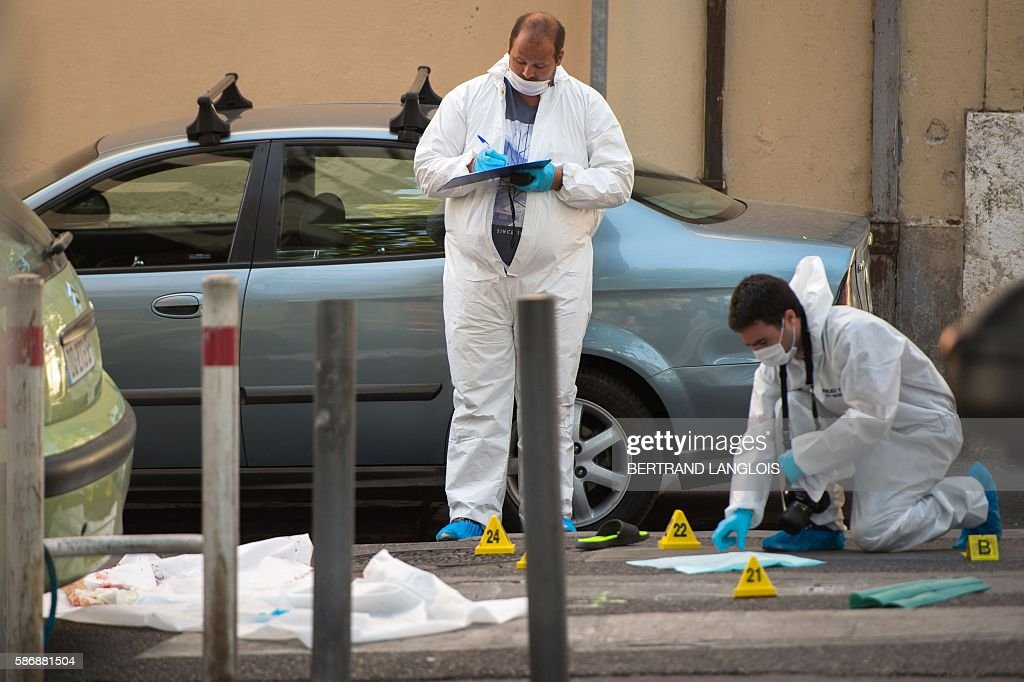 Forensic police officers investigate by the car where two men in their twenties were shot dead near the train station SaintCharles in Marseille...