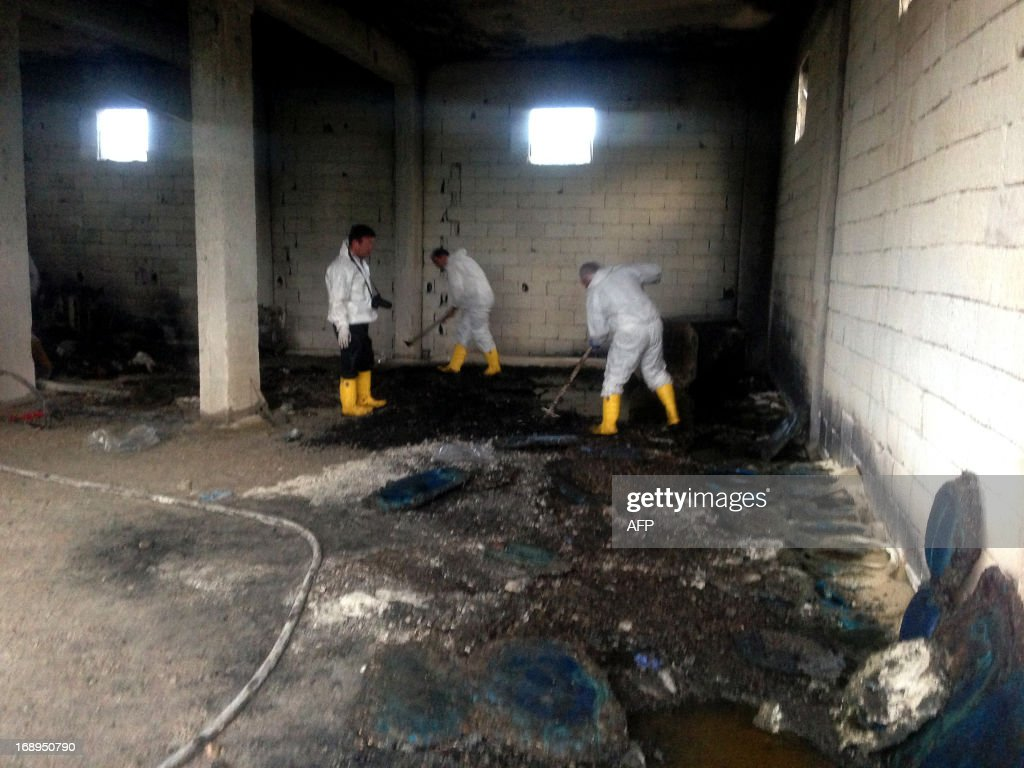 Forensic police officers work inside an illegal fuel depot on May 17, 2013, after suspects set ablaze the depot located in the basement of a three-storey building in a small village near Turkey's border with Syria, triggering a strong explosion that killed at least ten people and wounded nine others. Among the wounded were three suspected smugglers as well as several security officers, Anatolia news agency reported. AFP PHOTO / STR