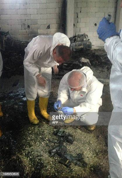 Forensic police officers work inside an illegal fuel depot on May 17 after suspects set ablaze the depot located in the basement of a threestorey...