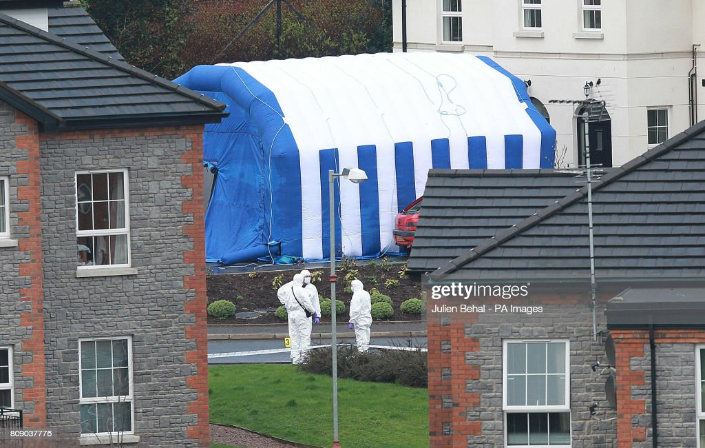 Forensic PSNI Officers work at the scene in Highfield Close, Omagh, where a young Catholic police officer was killed yesterday by a booby-trap car bomb in Northern Ireland.