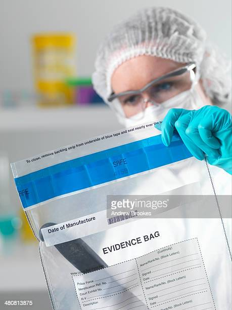 Forensic scientist holding evidence bag from crime scene in laboratory