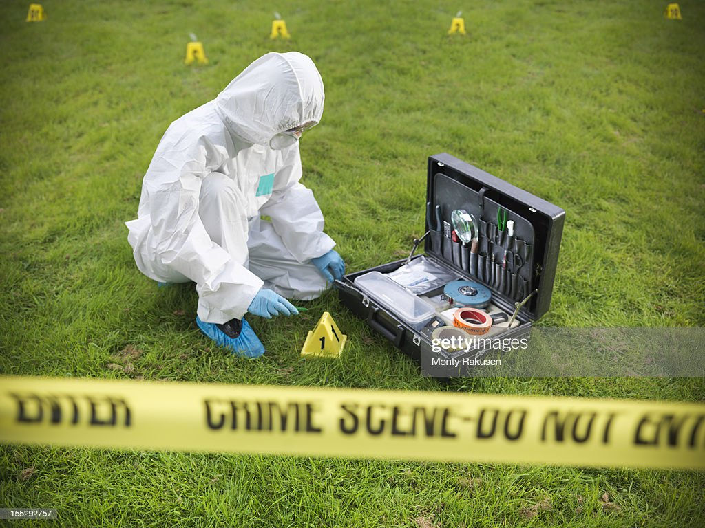 Forensic scientist inspecting toolkit at crime scene, police tape in foreground