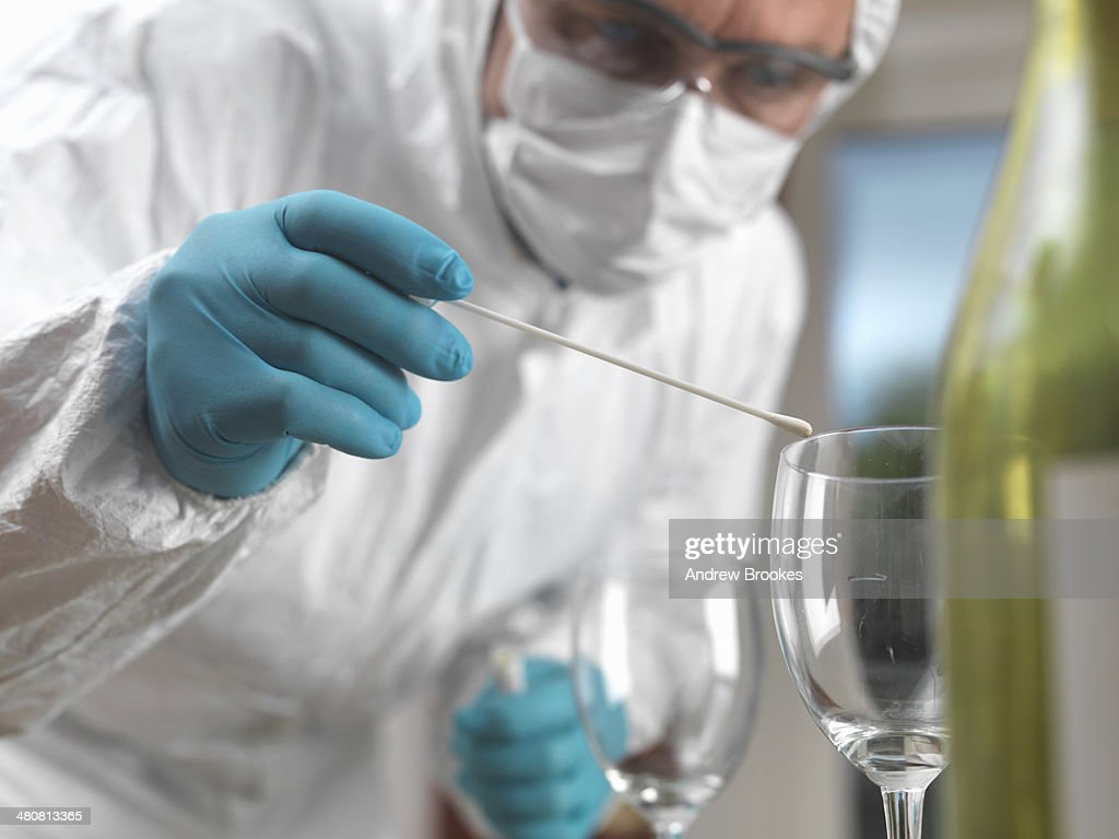 Forensic scientist using a DNA swab to take evidence from a glass at a scene of crime