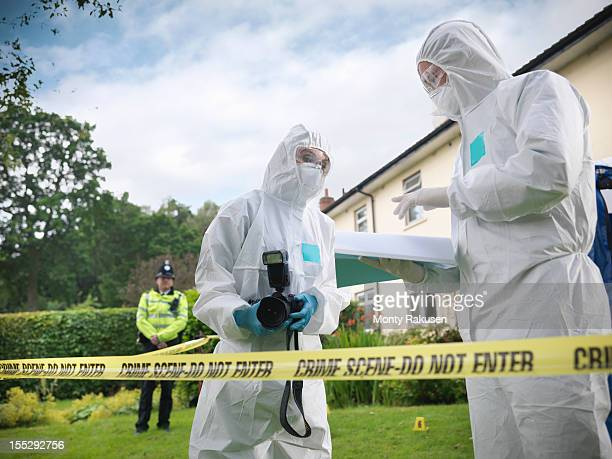 Forensic scientists in discussion at crime scene, one holding camera, policeman in background