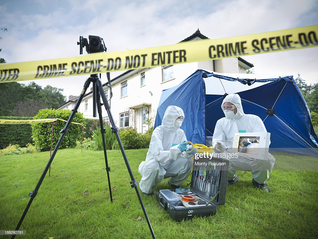 Forensic scientists with toolkit behind police tape at crime scene