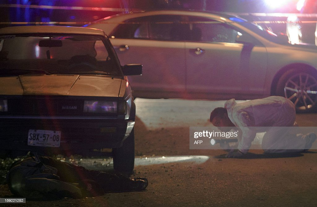 A forensic service officer (R) kneels as he looks at one of four corpses at a crime scene in Moderna town in the City of Monterrey, Nuevo Leon state on January 10, 2013. The three men and one woman were executed inside a house by gunmen according to the police.