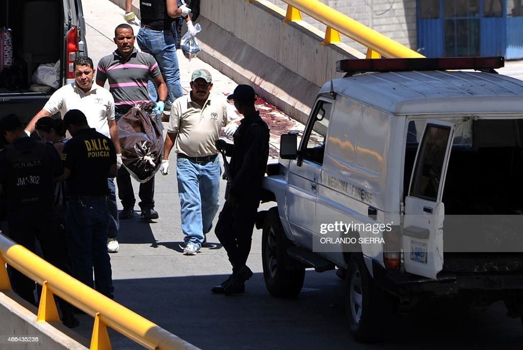 Forensic staffers carry the body of one of three models who were shot dead in the Valle de Angeles municipality in Tegucigalpa on March 15 2015 Two...