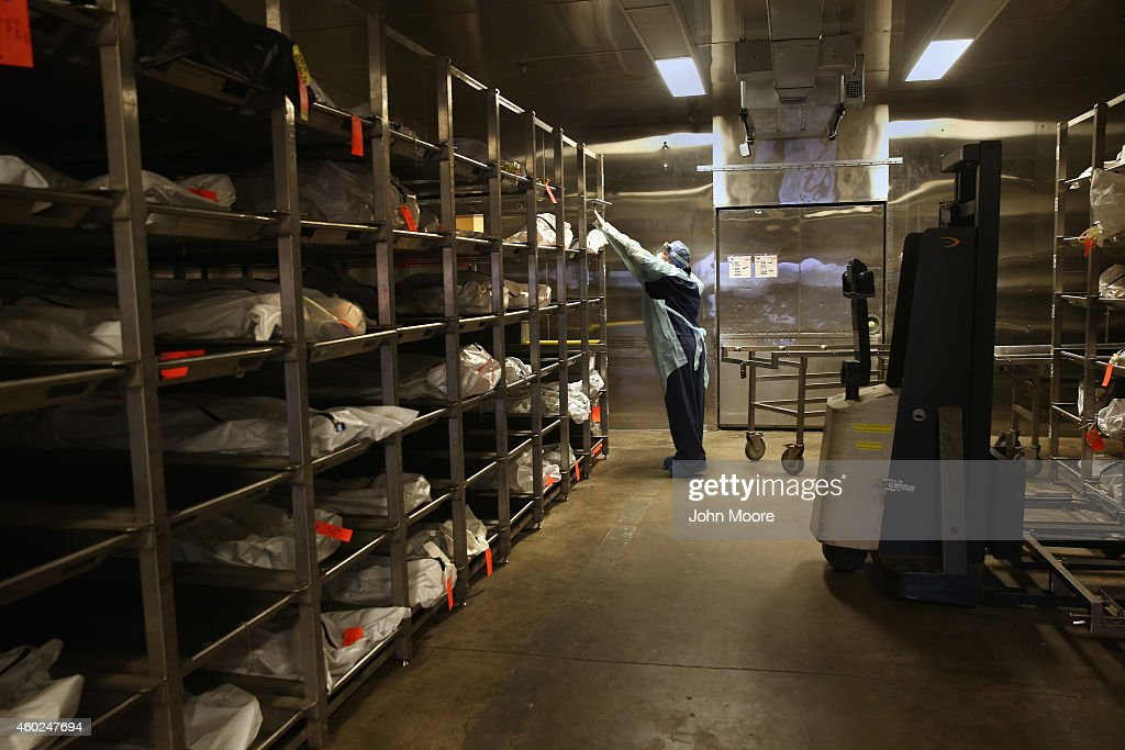 Forensic technician Kristine Clor handles human remains in the refrigerated morgue of the Pima County Office of the Medical Examiner on December 9...