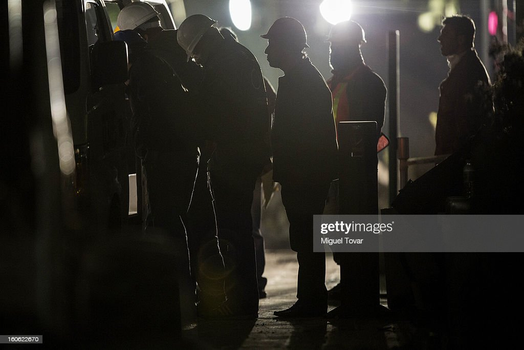 Forensic workers examine a body and keep searching for human bodies in affected levels of the administrative building of PEMEX on February 03, 2013 in Mexico City, Mexico. Authorities investigate a blast that killed at least 34 people at the state-owned companys headquarters in Mexico City.