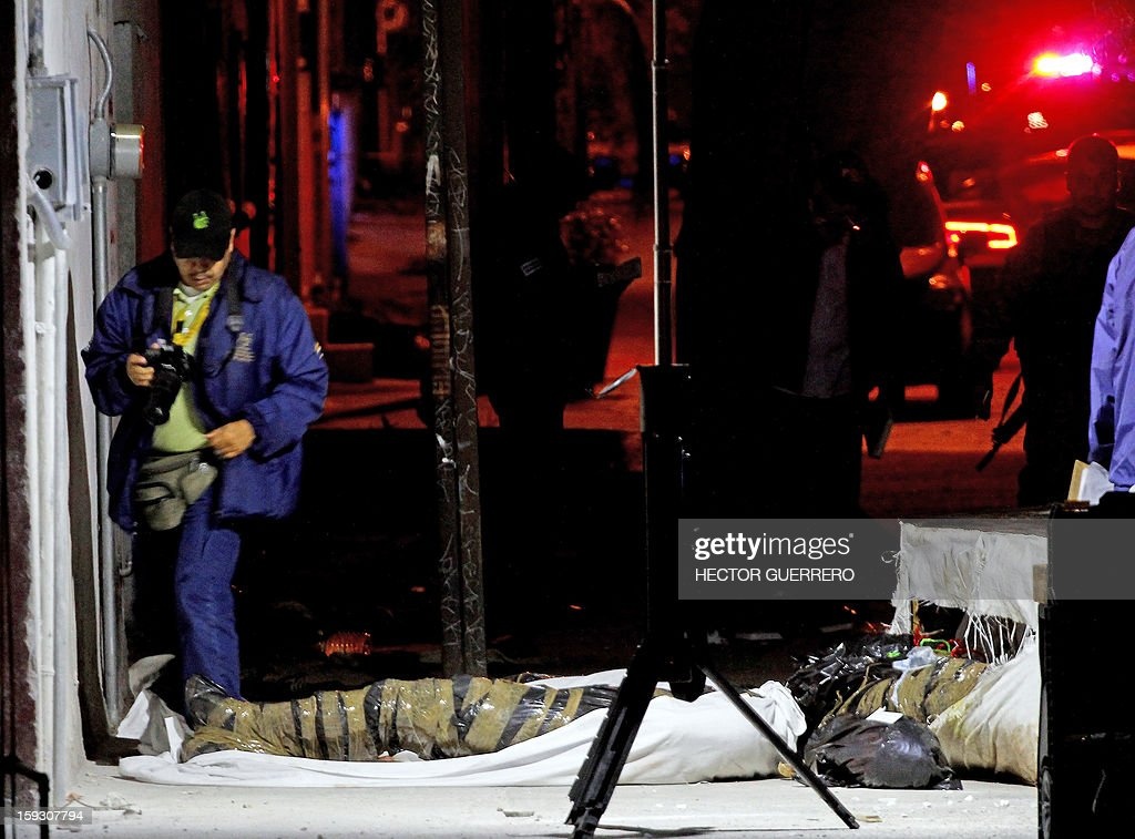 Forensics check human remains at a crime scene in Guadalajara city on January 11, 2013. Two men and one woman were beheaded and abandoned on a street inside trash bags. AFP PHOTO/Hector Guerrero