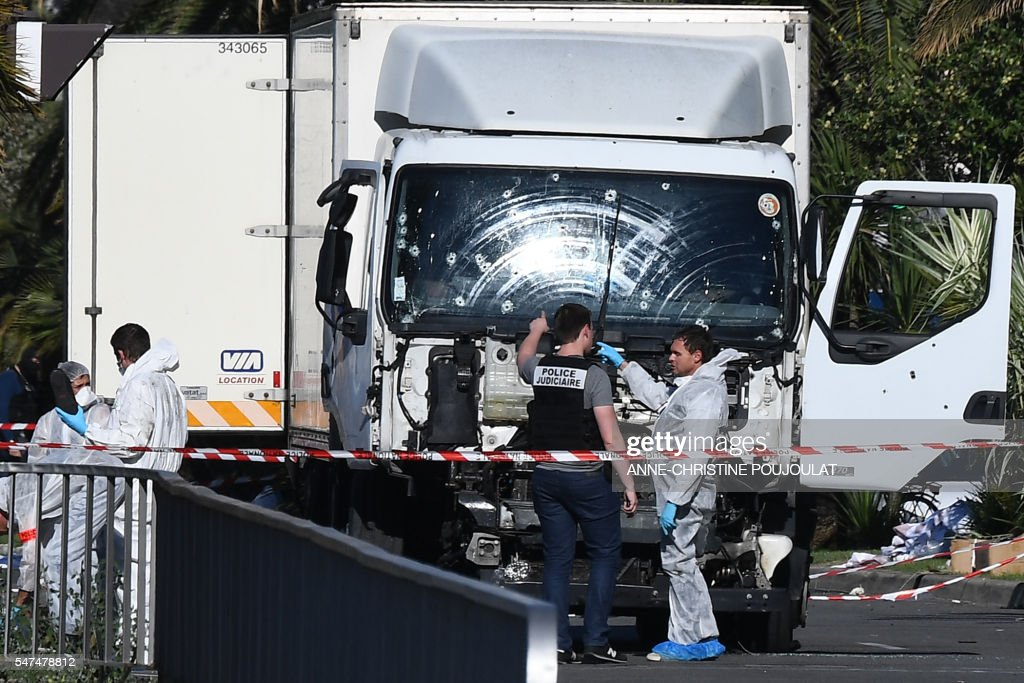 Forensics officers and policemen look for evidences near a truck on the Promenade des Anglais seafront in the French Riviera town of Nice on July 15, 2016, after it drove into a crowd watching a fireworks display. An attack in Nice where a man rammed a truck into a crowd of people left 84 dead and another 18 in a 'critical condition', interior ministry spokesman Pierre-Henry Brandet said Friday. An unidentified gunman barrelled the truck two kilometres (1.3 miles) through a crowd that had been enjoying a fireworks display for France's national day before being shot dead by police. POUJOULAT