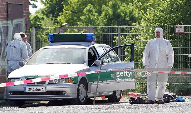 Forensics officers search a murder scene as the body of a shot policewoman lies on the ground at the Theresienwiese on April 25 2007 in Heilbronn...