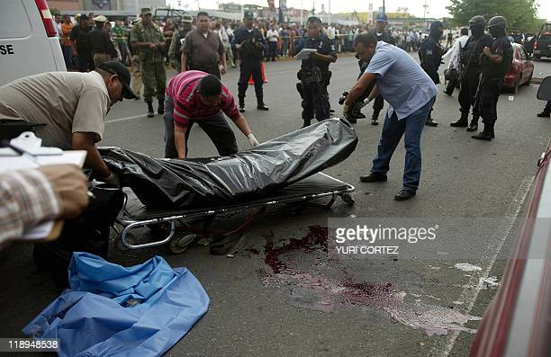 Forensics personnel remove the bodies of two policemen killed by gunmen during an attack on a street of Culiacan Sinaloa state on July 12 2011 Mexico...