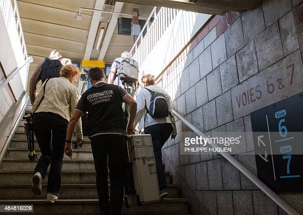 Forensics police walk up to the platforms at the train station of Arras northern France on August 22 after a gunman opened fire on a Thalys train...