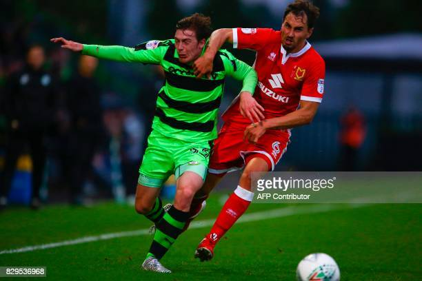 Forest Green Rovers' Luke James vies for the ball with MK Dons' Ed Upson during the EFL Cup football match between Forest Green Rovers and MK Dons at...