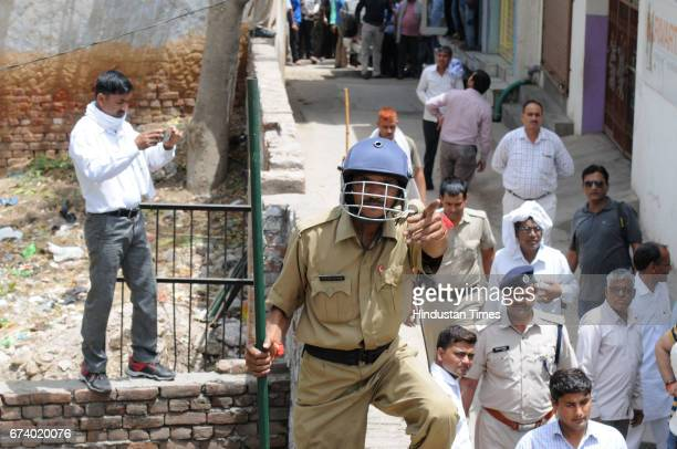A forest guard controls the people after a leopard entered a house in Durga Colony of Sohna locality on April 27 2017 some 25 km from Gurgaon India