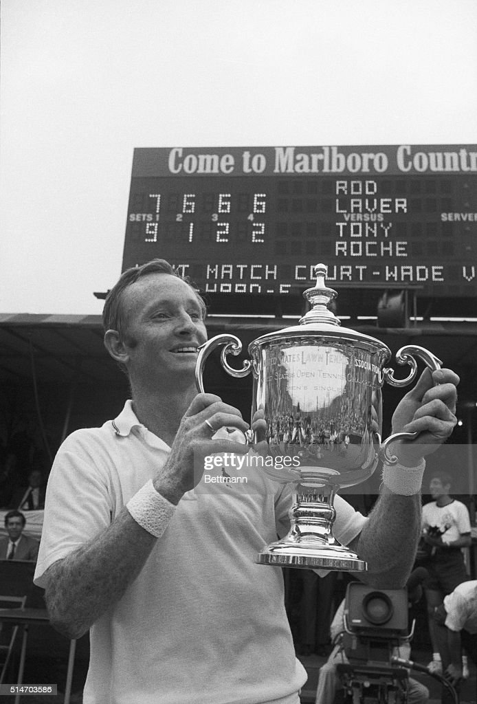 Rod Laver of Australia flashes a big grin as he holds the winner's trophy at the US Open Tennis Championships Sept. 8th. Scoreboard in the background tells the story of Laver's victory over Tony Roche--7-9, 6-1, and 6-2--in the final round. His victory clinched a grand slam, as he previously won the French, Australian and Wimbledon (English) titles to complete an unprecedented second grand slam. Laver won $16,000 as first prize money at Forest Hills. 9/8/1969