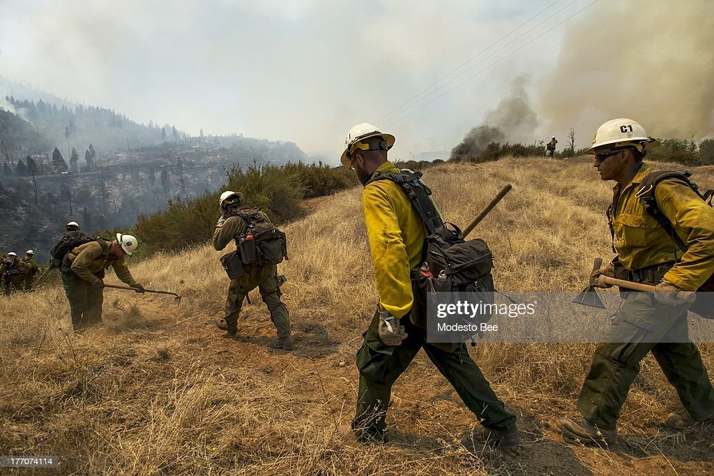 U.S. Forest Service firefighter head out to create a fire break to protect an electrical structure at the Rim Fire in the Stanislaus National Forest in California, Tuesday August 20, 2013.