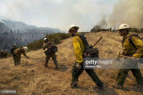 US Forest Service firefighter head out to create a fire break to protect an electrical structure at the Rim Fire in the Stanislaus National Forest in...