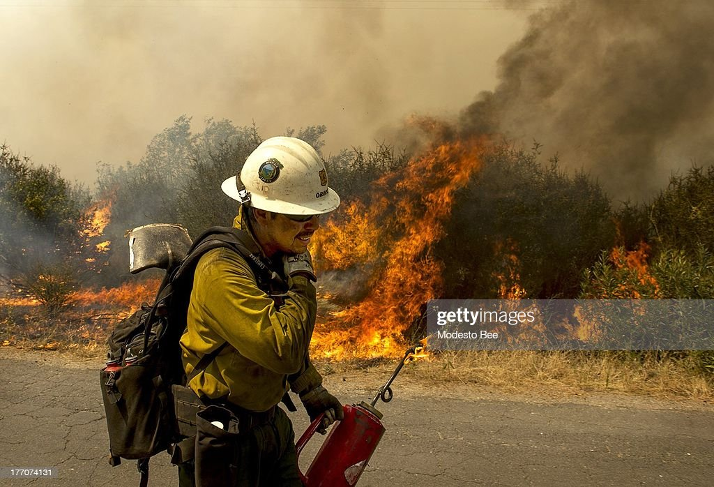 U.S. Forest Service firefighter moves away from a quickly moving section of the Rim Fire in the Stanislaus National Forest in California, Tuesday August 20, 2013.