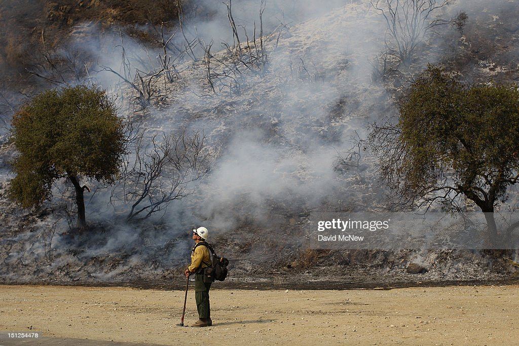 S. Forest Service firefighter stands near a smoldering hillside at the Williams fire in the Angeles National Forest on September 4, 2012 north of Glendora, California. The fire began late September 2, putting an early end to Labor Day weekend camping and hiking for vacationers, who were evacuated from the area as it spread to more than 4,000 acres in size. Officials project that it will take at least another week to establish a containment line around the fire which is burning in rugged and difficult to reach backcountry.
