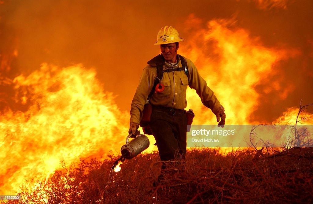 S Forest Service firefighter uses a drip torch to set a backfire on the Los Coyotes Indian Reservation to fight a fire rushing through upper Borrego...