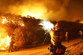 S Forest Service firefighter uses a pistol to fire flares into brush to set a backfire to control the Woodhouse fire also being called the Calimesa...