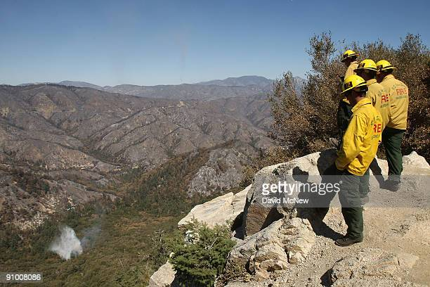 S Forest Service firefighters from San Bernardino County watch a firefighting helicopter they requested drop water on a spot fire near the Mount...