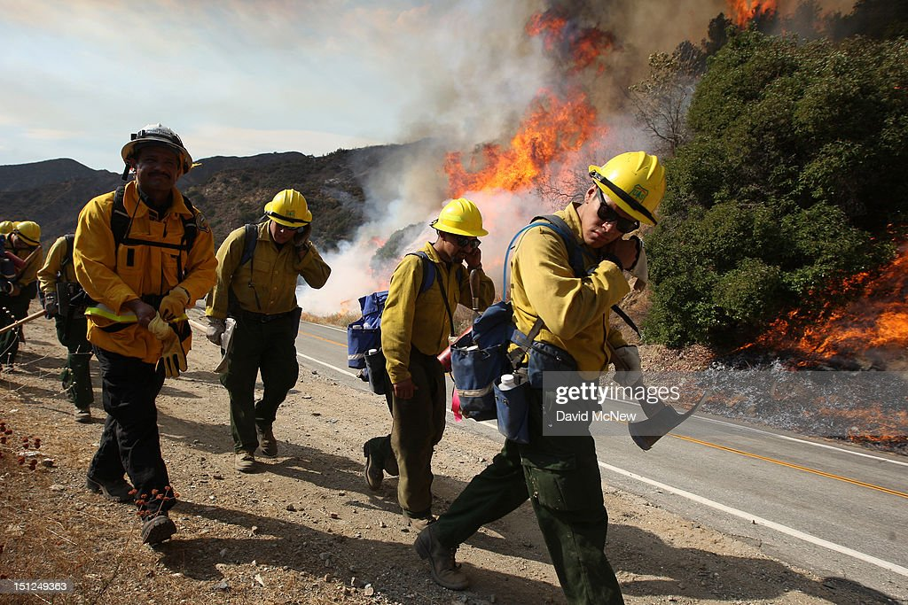 U.S. Forest Service firefighters shield their faces from the heat of flames along a road at the Williams fire in the Angeles National Forest on September 4, 2012 north of Glendora, California. The fire began late September 2, putting an early end to Labor Day weekend camping and hiking for vacationers, who were evacuated from the area as it spread to more than 4,000 acres in size. Officials project that it will take at least another week to establish a containment line around the fire which is burning in rugged and difficult to reach backcountry.