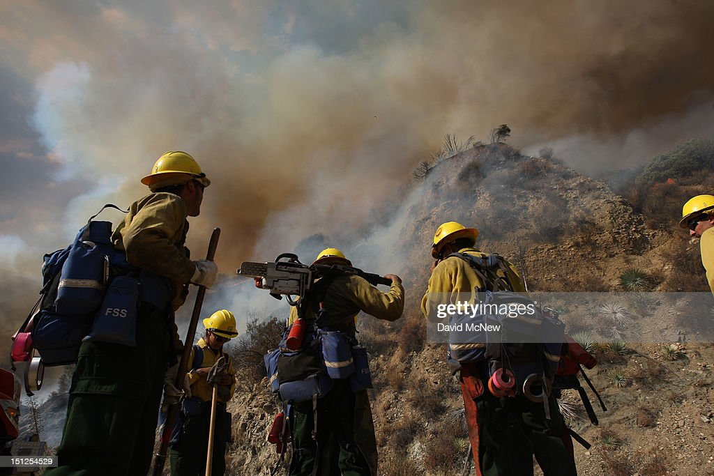 U.S. Forest Service firefighters stand near a smoldering hillside at the Williams fire in the Angeles National Forest on September 4, 2012 north of Glendora, California. The fire began late September 2, putting an early end to Labor Day weekend camping and hiking for vacationers, who were evacuated from the area as it spread to more than 4,000 acres in size. Officials project that it will take at least another week to establish a containment line around the fire which is burning in rugged and difficult to reach backcountry.