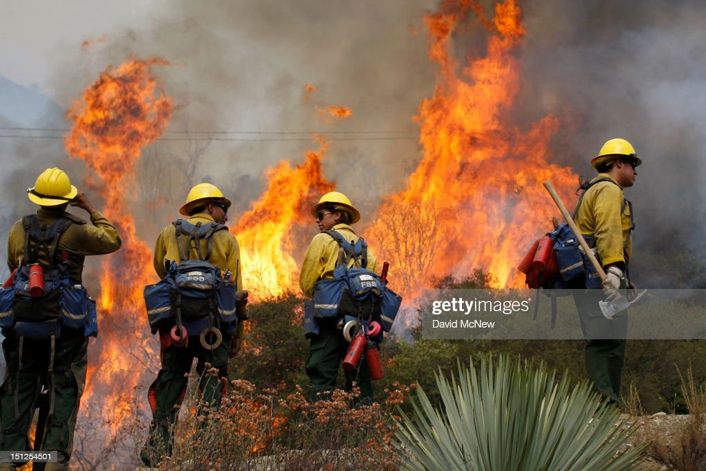 U.S. Forest Service firefighters stand near flames at the Williams fire in the Angeles National Forest on September 4, 2012 north of Glendora, California. The fire began late September 2, putting an early end to Labor Day weekend camping and hiking for vacationers, who were evacuated from the area as it spread to more than 4,000 acres in size. Officials project that it will take at least another week to establish a containment line around the fire which is burning in rugged and difficult to reach backcountry.