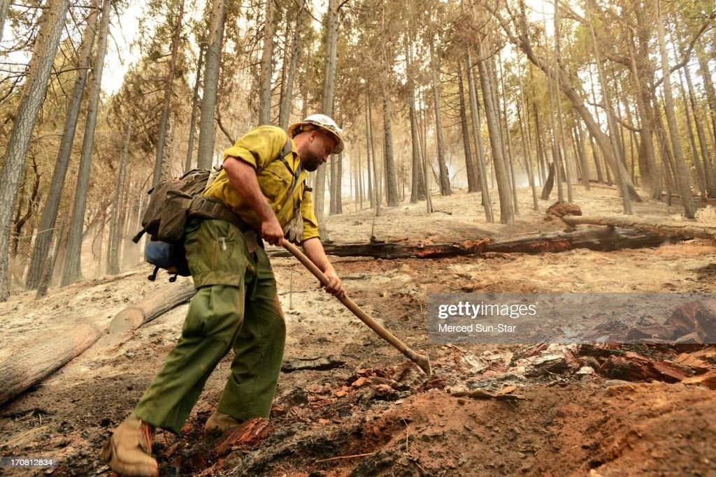 U.S. Forest Service fireman Bo Rice, 28, works on putting out hot spots on fire division line Oscar using a hoe and a 2,500 foot hose line while fighting the Carstens Fire in the Sierra National Forest near Jerseydale in the Mariposa area, June 17, 2013.