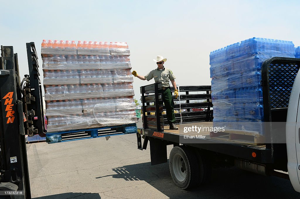 U.S. Forest Service technical specialist Shawnee Hinman loads drinks for fire crews on a truck at the incident command post for the Carpenter 1 fire at Centennial High School on July 10, 2013 in Las Vegas, Nevada. More than 25,000 acres have burned since lightning sparked the blaze in Carpenter Canyon on the Pahrump, Nevada side of Mount Charleston on July 1. More than 1,000 firefighters are battling the wildfire which crested the peak of Mount Charleston on July 4, prompting the evacuation of 520 people as it began descending the east side of the mountain, about 35 miles northwest of Las Vegas. The fire is 10% contained and fire officials estimate that they won't have it fully contained until July 19.