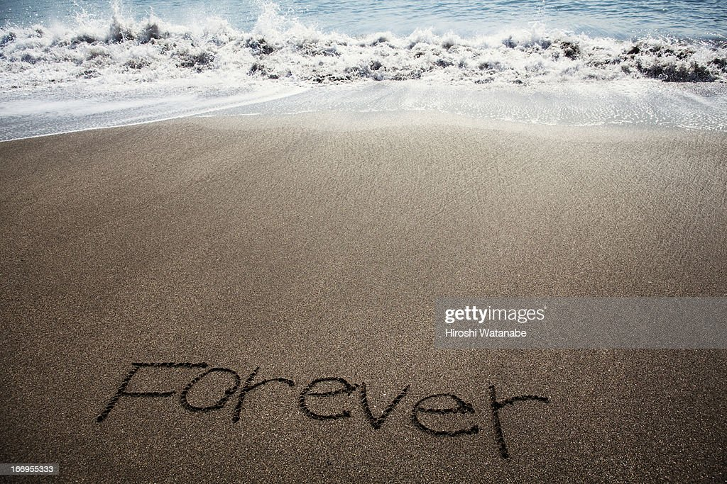 'Forever' written in sand on beach