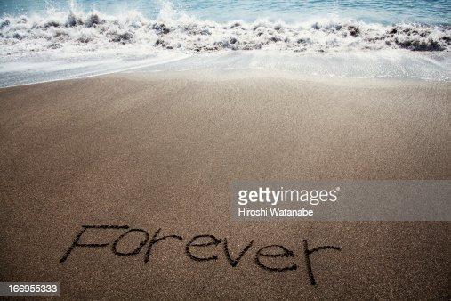'Forever' written in sand on beach : Foto de stock