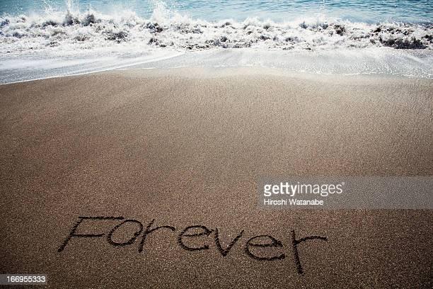 'Forever' written in sand on beach