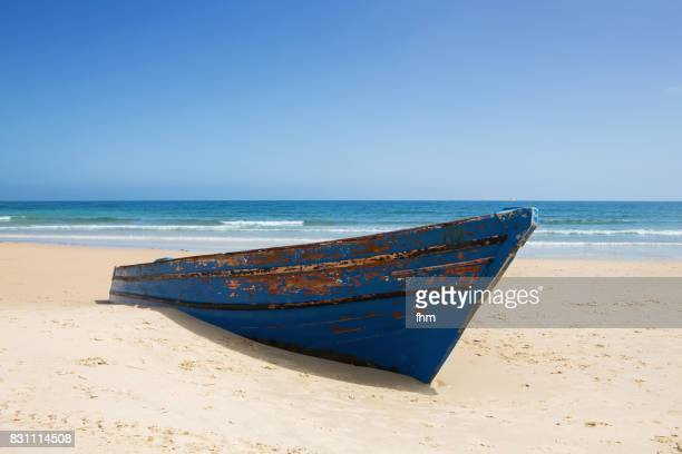 Forgotten rowboat on the beach, partially buried in the sand