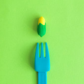 Flat lay of plastic fork and small rubber corn toy against green background minimal creative vegetarian concept.