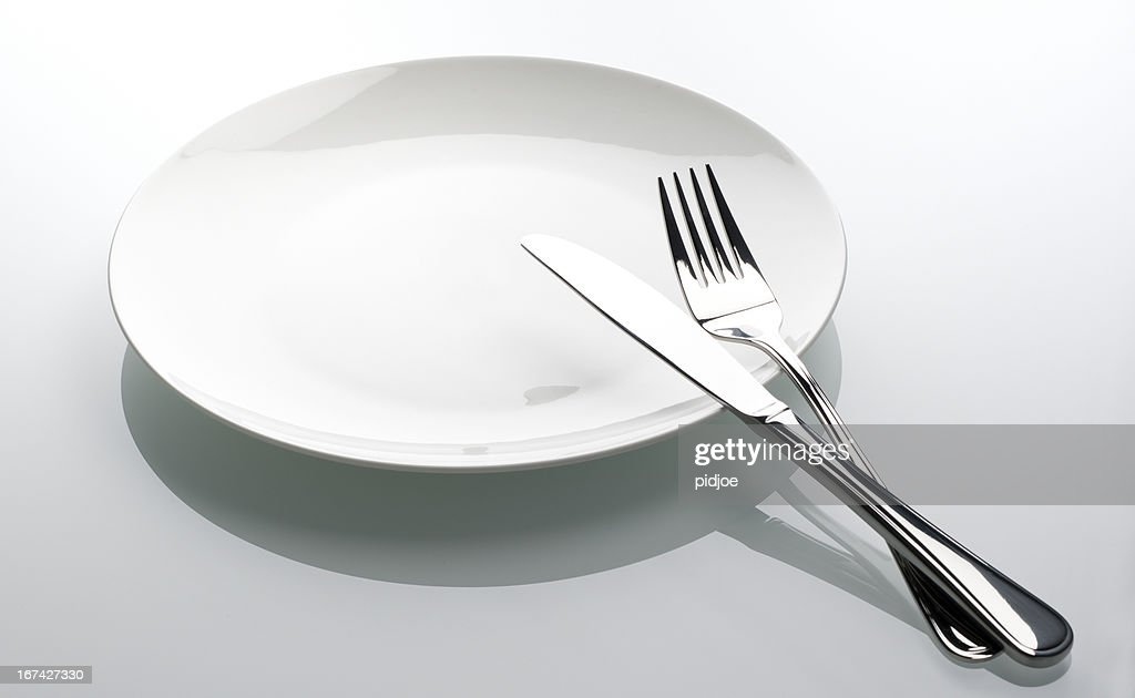 fork and knife on empty white plate : Stock Photo
