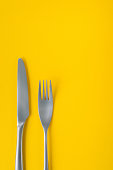 Fork and knife on yellow background, sparse composition with copy space. Dinner theme template and background