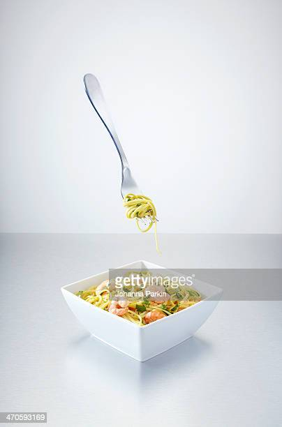 Fork hovering mid-air above bowl of prawn noodles