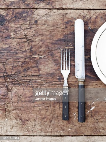 Fork, knife and plate on wooden table, directly above