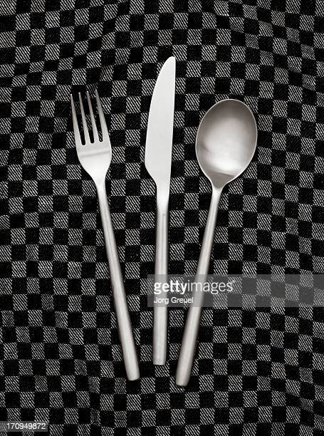 Fork, knife and spoon on dishcloth