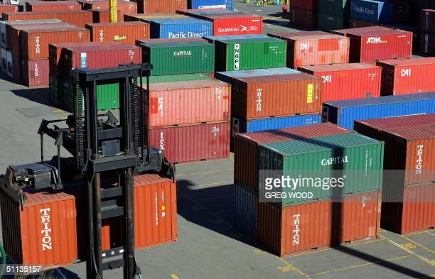 A fork lift moves export shipping containers stacked on a wharf at Darling Harbour in Sydney 02 August 2004 Australia's controversial free trade...