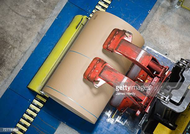 Fork lift picking up roll of paper